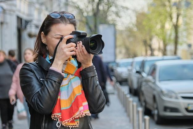 Fällige frau mit fotokamera fotografierend auf der straße