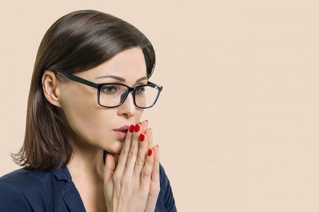Fällige frau mit gläsern faltete ihre betenden arme meditiert, nahaufnahmebeige, exemplarplatz.