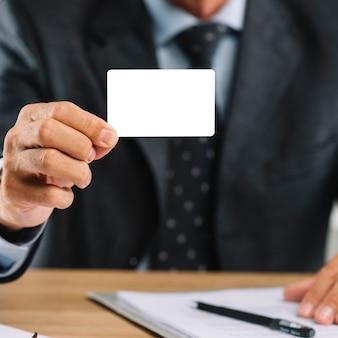 Fälliger geschäftsmann, der leere visitenkarte zeigt