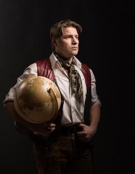 Fälliger mann im kostüm des reisenden alte kugel halten
