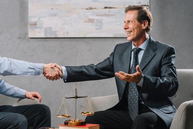 Fälliger rechtsberater, der hand mit kunden im büro rüttelt