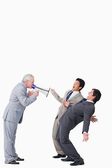 Fälliger verkäufer mit megaphon schreiend an seinen angestellten