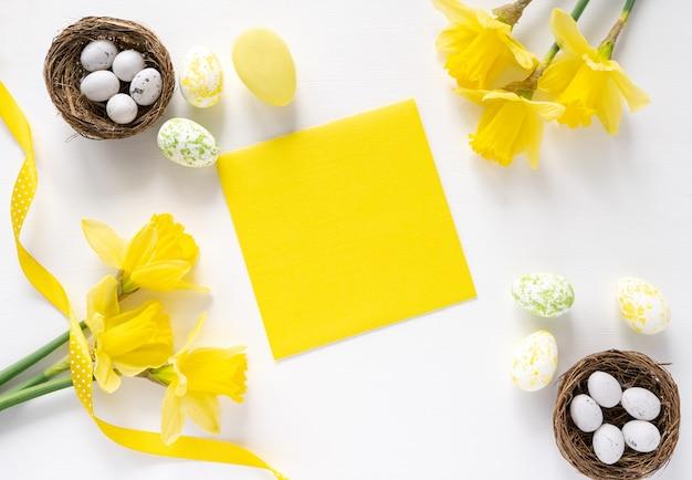 Färben sie ei ostern und gelben blumenstrauß auf weißem hintergrund, kopienraum, draufsicht, grußkarte. osterhintergrund