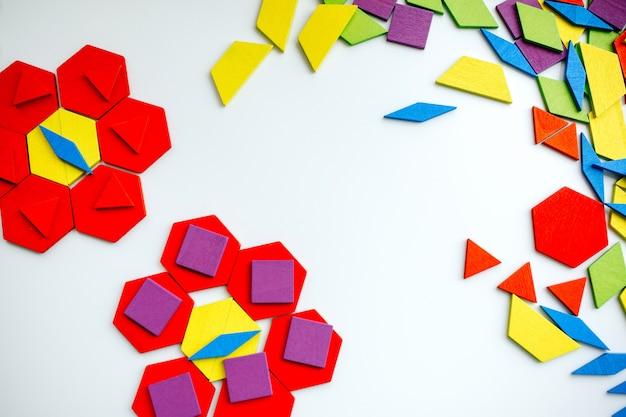Färben sie hölzernes tangrampuzzlespiel in der blumenform auf weißem hintergrund