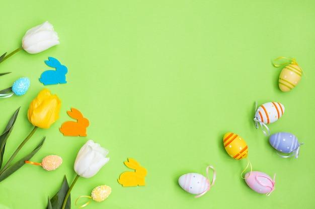 Färben sie ostereier und häschen mit weißen, gelben tulpen auf einem grünen hintergrund.