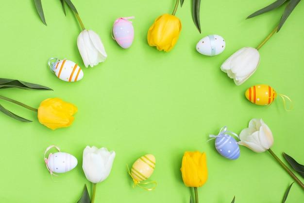 Färben sie ostereier und weiße gelbe tulpen auf einem grünen hintergrund.