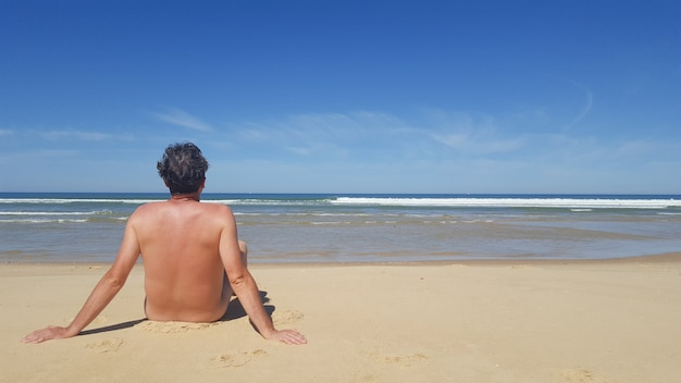 Färben sie porträtfoto eines nackters, der allein auf dem strand sitzt