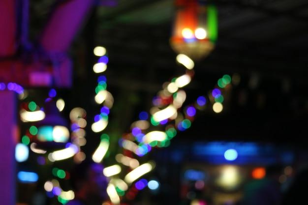Färben sie zusammenfassung des unschärferegenbogen-lichtinnenraums auf baum im nachtgarten
