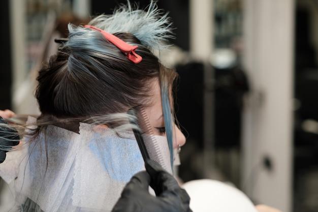 Färbendes haar des friseurs der kundin, während sie im stuhl sitzt