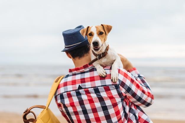 Fahionable männlicher wirt des schönen hundes, trägt ihn auf händen, kommt, um bei sonnenuntergang auf küste zu sehen