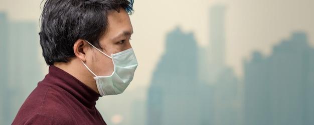 Fahne des asiatischen mannes die gesichtsmaske gegen luftverschmutzung am balkon tragend