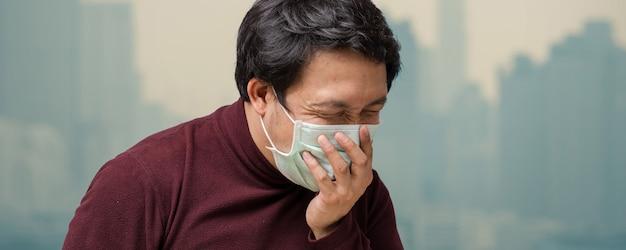 Fahne des asiatischen mannes die gesichtsmaske gegen luftverschmutzung tragend