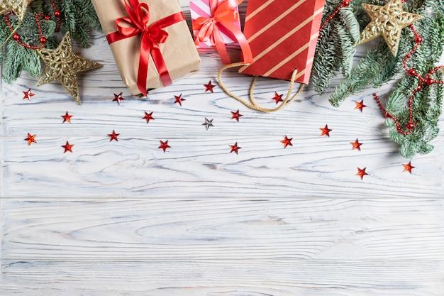 Fahne mit cristmas geschenken und dekorationen auf weißem hölzernem hintergrund mit funkelnden sternen