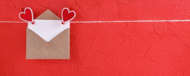 Fahne mit leerem blatt papier im umschlag hängt an einem seil, das mit herz-förmigen wäscheklammern für valentinstag befestigt wird