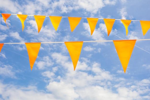 Fahnen in der niederländischen nationalfarbe orange am strahlend blauen himmel mit sonnenlicht zum feiern des königstages king