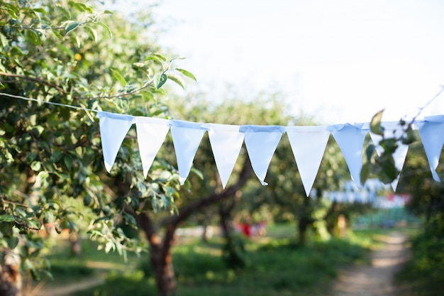 Fahnengeburtstagsdekorationen, die am ast im garten hängen. bunte flaggenfahnen, die im park hängen. gartenparty dekoration.