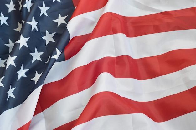 Fahnenschwingen der vereinigten staaten von amerika mit vielen falten