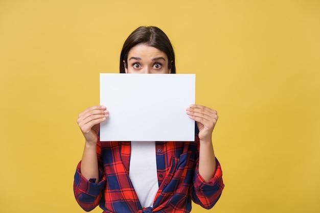 Fahnenzeichenfrau, die über rand des leeren leeren papiers späht