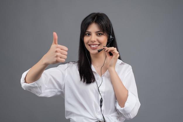 Fahrdienstleiter mit dem kopfhörer, der geschäftstelefonanrufe beantwortet und die daumen oben lokalisiert über grau zeigt