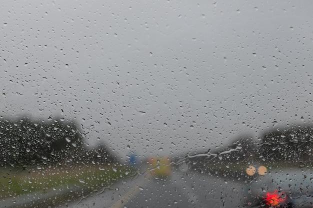 Fahren im regen. regentropfen auf der autoglasoberfläche. abstrakter verkehr am regentag. blick vom autositz. straßenansicht durch autofenster mit regentropfen, selektiver fokus.