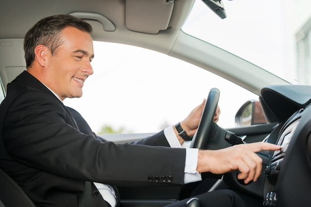 Fahren mit komfort. seitenansicht eines fröhlichen reifen mannes in formaler kleidung, der auto fährt und das armaturenbrett mit dem finger berührt