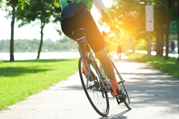 Fahren sie mit dem fahrrad auf der straße im stadtpark. sport und aktives lebenkonzept in der sommerzeit
