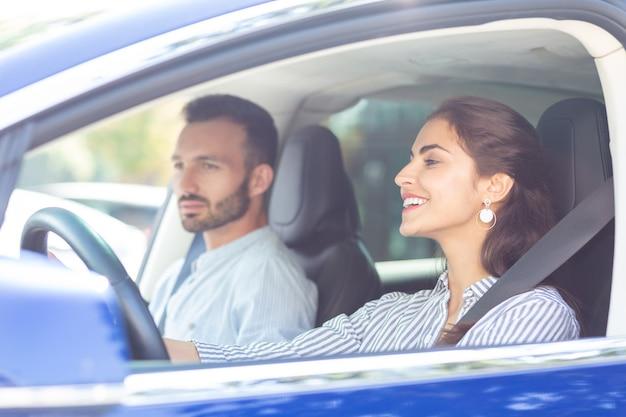 Fahren und sprechen. ansprechende schöne frau, die auto fährt und mit ihrem gutaussehenden ehemann spricht
