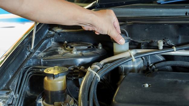 Fahrer, der das auto vor gebrauchtem oder mechanischem service überprüft