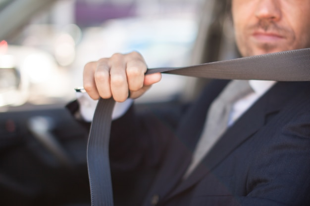 Fahrer, der den sicherheitsgurt seines autos befestigt. geringe schärfentiefe, fokus auf die hand