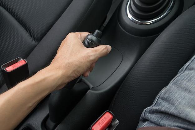 Fahrer, der die handbremse im auto zieht