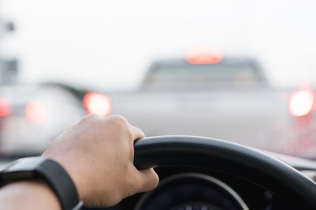 Fahrer, der ein lenkrad oben hält (12-uhr-position), während er ein auto auf einer stark befahrenen straße fährt. asiatischer fahrer, der ein fahrzeug auf autobahnnahaufnahme fährt.