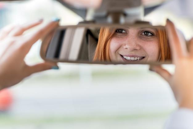 Fahrer der jungen frau, der rückspiegel prüft, der rückwärts schaut, während ein auto fährt.
