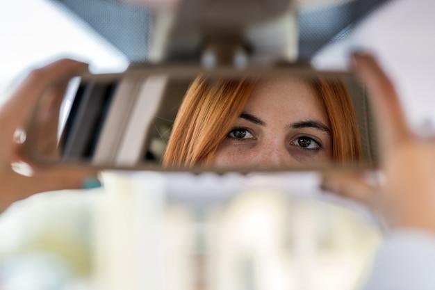 Fahrer der jungen frau, der rückspiegel prüft, der rückwärts schaut, während ein auto fährt
