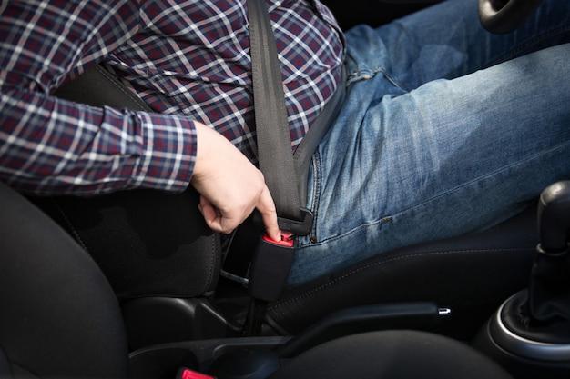Fahrer des jungen mannes, der die rote sicherheitsgurttaste im auto drückt