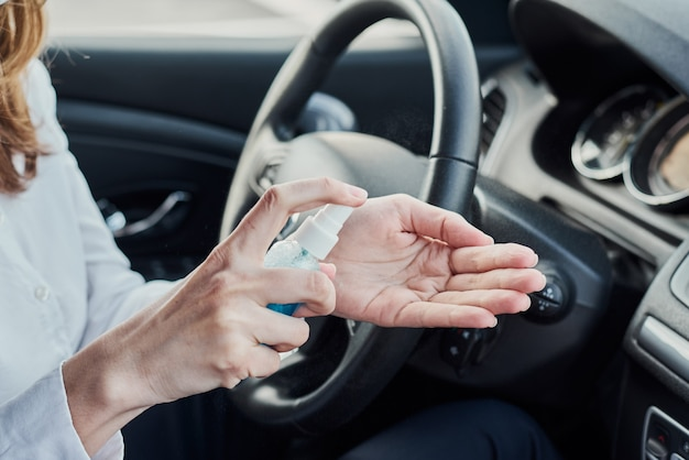 Fahrer desinfektion hände mit antibakteriellem spray im auto vor dem fahren