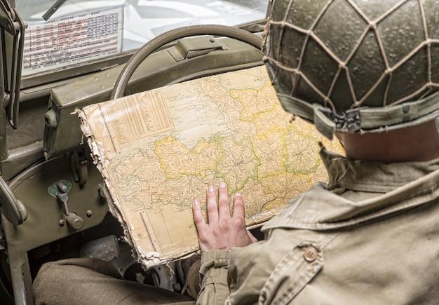 Fahrer eines militärfahrzeugs blick auf eine karte der normandie