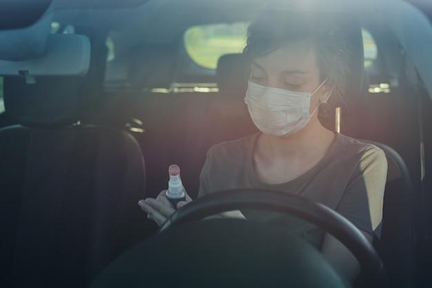 Fahrer mit einem händedesinfektionsmittel im auto