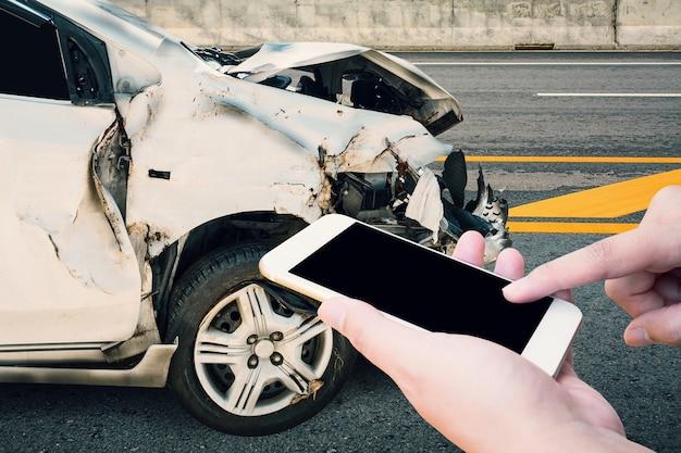 Fahrer mit mobilem smartphone mit autounfall auf der straße