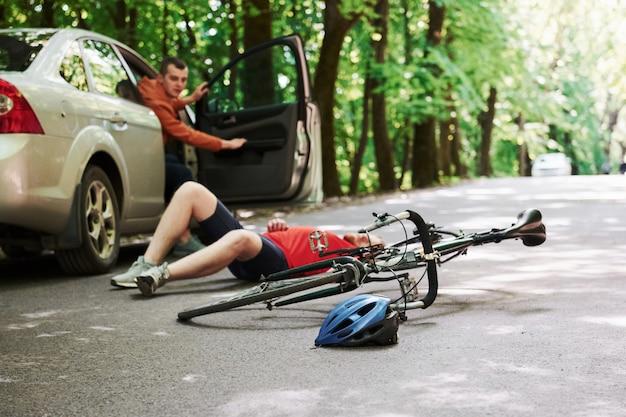 Fahrer öffnet die tür. opfer auf dem asphalt. fahrrad und silberfarbener autounfall auf der straße am wald während des tages