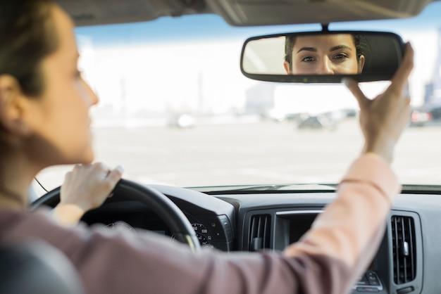 Fahrer stellt den rückspiegel ein