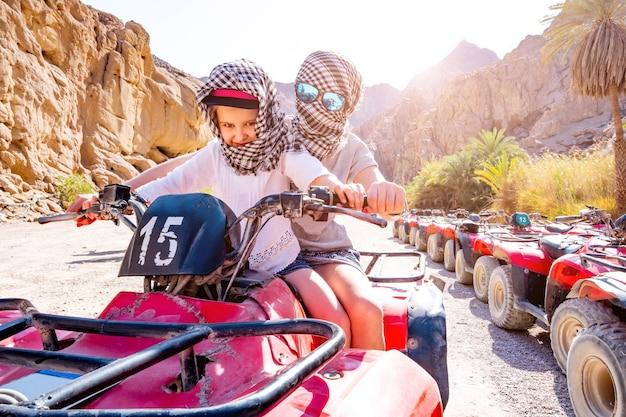 Fahrer und kind, die ein quad in der wüstensafari fahren