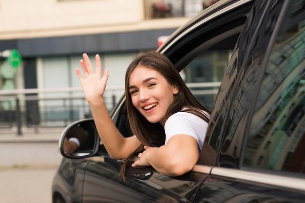 Fahrerfrau des autos winkt zurück als zeichen des abschieds auf der straße