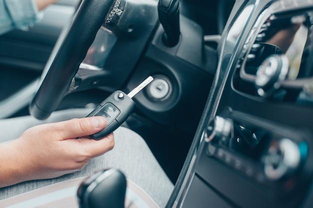 Fahrerin, die das auto durch autoschlüssel, transportkonzept startet