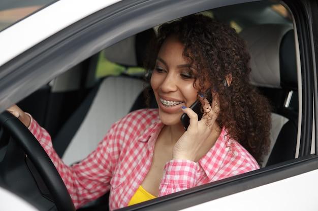 Fahrerin, die ein auto fährt, ist am telefon abgelenkt und schaut zur seite