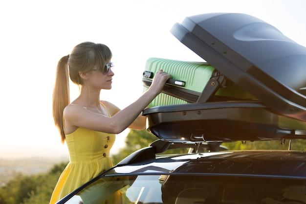 Fahrerin, die grünen koffer in ihren autodachkofferraum einsetzt. reise- und urlaubskonzept.