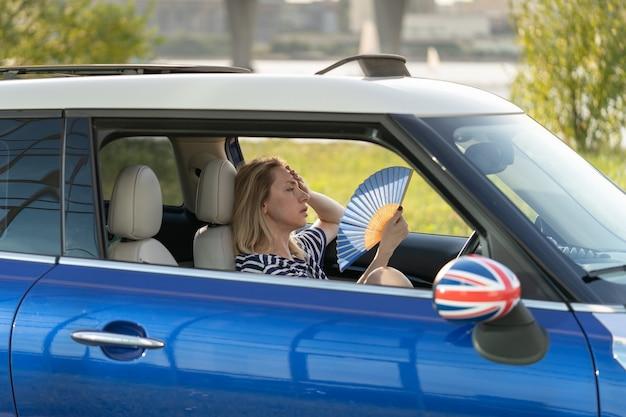 Fahrerin mit handlüfter, die im auto unter hitze leidet, hat ein problem mit einer nicht funktionierenden klimaanlage