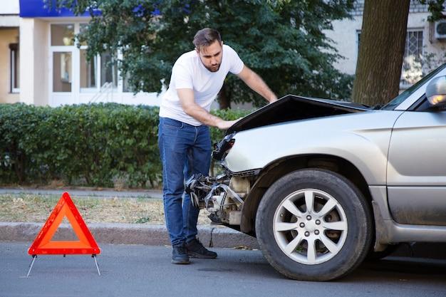 Fahrermann, der auf autowrack bei autounfall schaut. mann bedauert, auto nach autounfall repariert zu haben. tragödie autokollision. gefährliche verkehrssituation.