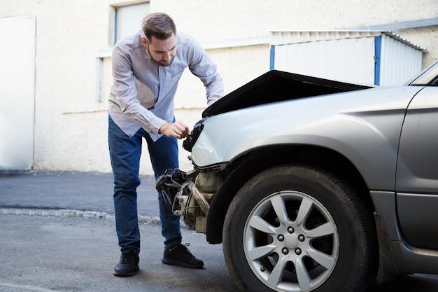 Fahrermann, der auf autowrack bei autounfall schaut. mann bedauert, autoscheinwerfer nach autounfall repariert zu haben. tragödie autokollision. gefährliche verkehrssituation.