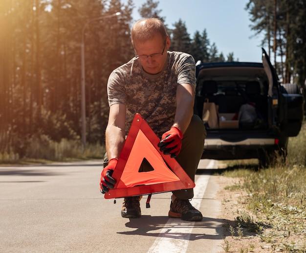Fahrermann, der im sommer ein dreieck-warnschild auf die straße in der nähe von kaputtem auto setzt