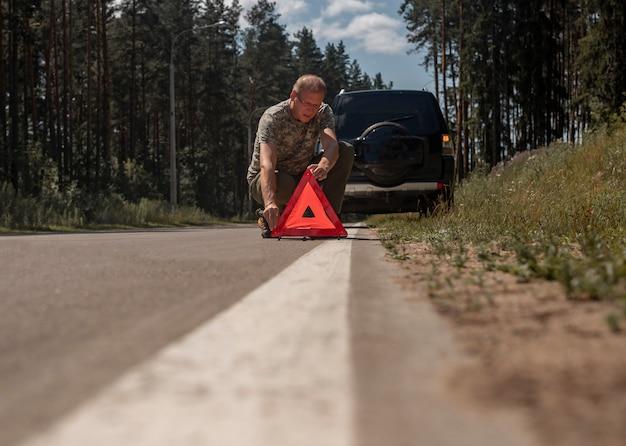 Fahrermann setzt rotes dreieck vorsicht und warnschild auf straße in der nähe von kaputtem auto
